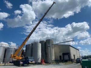 installation d'une passerelle en acier inoxydable à dix mètres de hauteur par un camion grue sous un beau ciel bleu