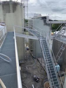 Vue de haut d'une passerelle en inox avec escalier entre des cuves de 10 m de hauteur
