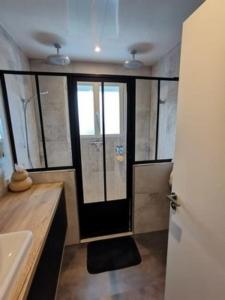 Photo d'une salle de bain avec une verrière noire créée sur mesure par VOLUMETAL